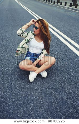 Trendy young fashion model posing with skate board wearing colorful sunglases summer time