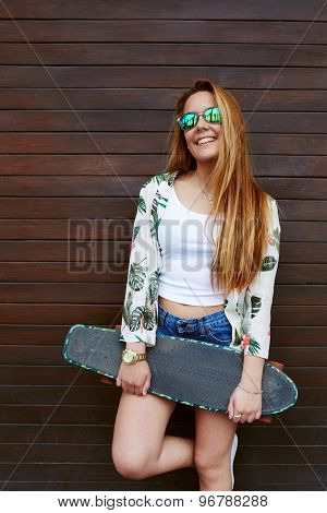 Female hipster in sunglases standing against wooden wall background and enjoying good summer day