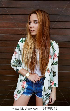 Portrait of a beautiful hipster girl wearing trendy clothing standing on wooden wall background