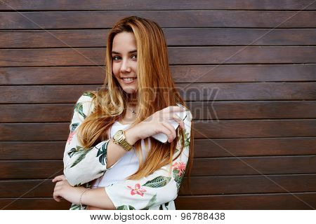 Gorgeous smiling female standing with mobile phone against wooden wall background with copy space