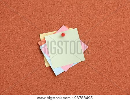 Cork board with colorful notes and red pin