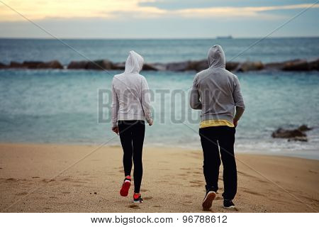 Young sporty man and woman talking each to other while taking break after run all the seashore