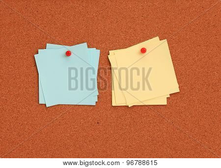 Cork board with blue and yellow notes and red pin