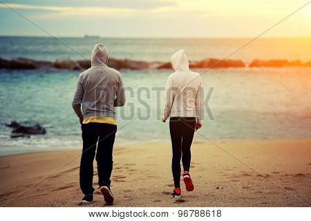 Sporty couple walking on the beach while they rest after intense morning training outdoors