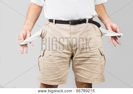 Man in shorts pulling out his empty pockets