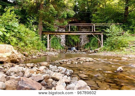 Mountain Stream Flows Through The Old Stone Archway In The Forest