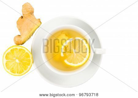 Hot ginger and lemon tea in a cup with sliced lemon and ginger roots