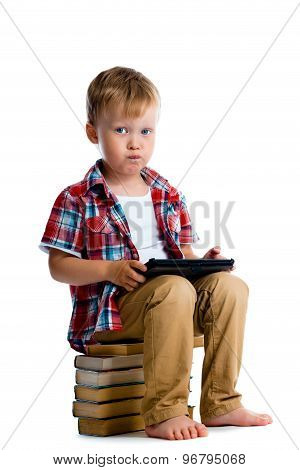 Little Boy With A Tablet Computer Sitting On The Books