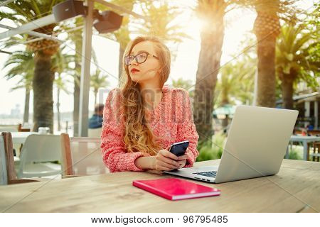 Portrait of young creative woman work on laptop while having breakfast  in modern coffee shop