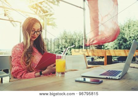 Attractive female freelancer reading notebook while sitting at wooden table front open computer