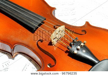 Violin Isolated On White Background And Sheet Music Behind