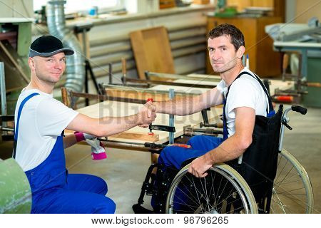 Worker In Wheelchair In A Carpenter's Workshop With His Colleague