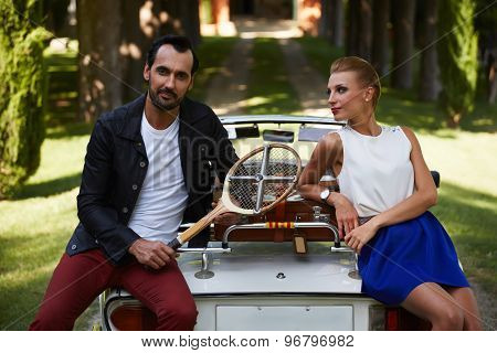 Happily married couple enjoying a beautiful day outdoors while leaning on their convertible antique