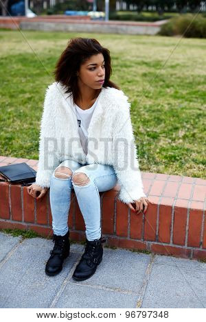 Attractive female hipster dressed in cute stylish clothing sitting outdoors in the park
