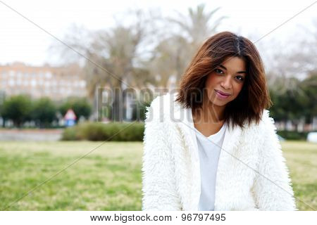 Female hipster in stylish clothing posing to the camera while sitting outdoors in beautiful park