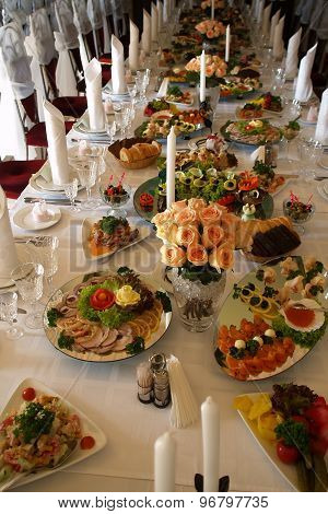 Long spread served festively decorated table with rose bouquets