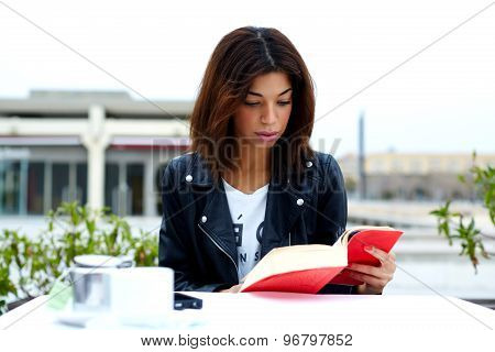 Young lovely female enjoying a good book while sitting at the table in coffee shop terrace