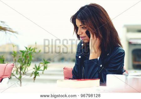 Attractive afro american woman talking on the smart phone while sitting at coffee shop terrace