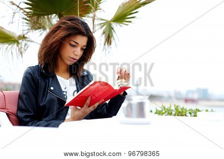 Young brunette woman relaxing at weekend while read interesting book outdoors in cafe restaurant