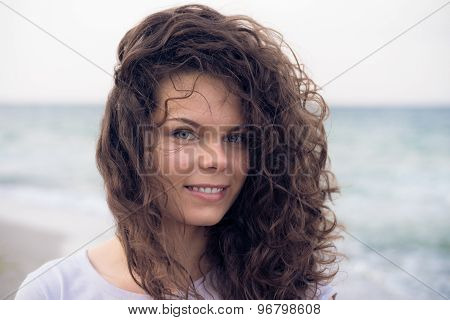 Portrait Of A Young Cute Smiling Woman With Brown Curly Hair Close-up