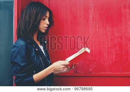 Young female student reading interesting book while standing in the city on red wall background