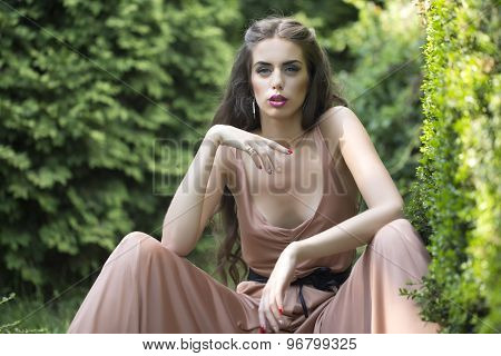 Sensual Woman Sitting In Garden
