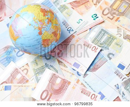 Earth globe over the pile of money