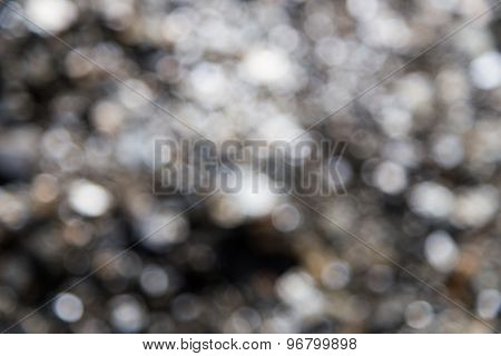 De-focused background of a pile of shinny stones under bright sun