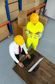 stock photo of warehouse  - Elevated View Of Warehouse Worker And Manager Using Computer In A Warehouse - JPG