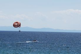 stock photo of parasailing  - Motor white boat parasailing alone in the blue sea - JPG