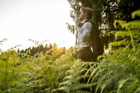 stock photo of stressless  - Young Businessman Holding is Coat Over his Shoulder Standing in the Forest and Looking into the Distance at the Afternoon - JPG