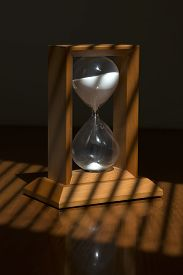 foto of jalousie  - Old fashioned retro wooden hour glass clock with white sand standing on table top with jalousie shadow from sun through window vertical picture - JPG