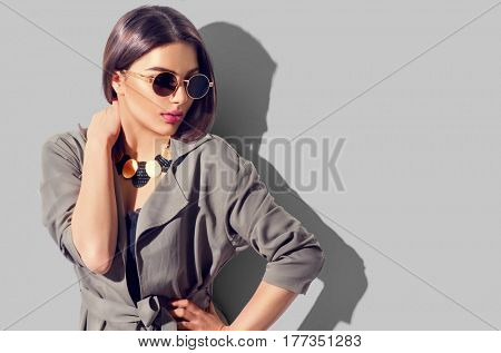 poster of Beauty Fashion brunette model girl wearing stylish coat and sunglasses. Sexy woman portrait with per