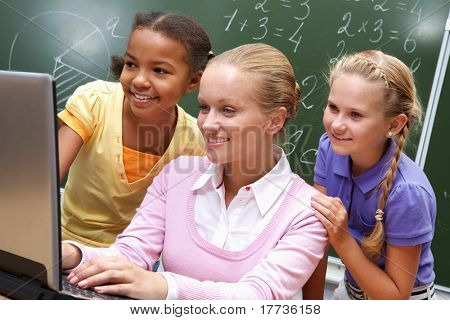 Portrait of two girls and teacher looking at the laptop in classroom