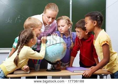 Portrait of pupils looking at globe while listening to teacher during geography lesson