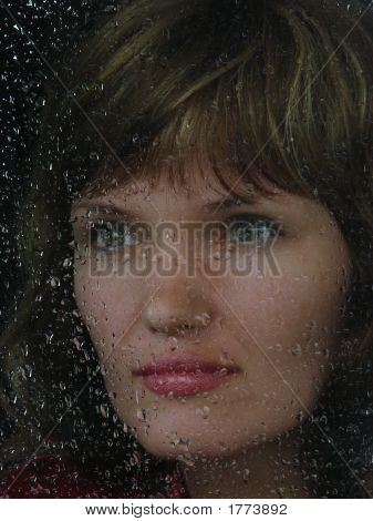 Girl Looks Thru Waterdropped Widow Glass