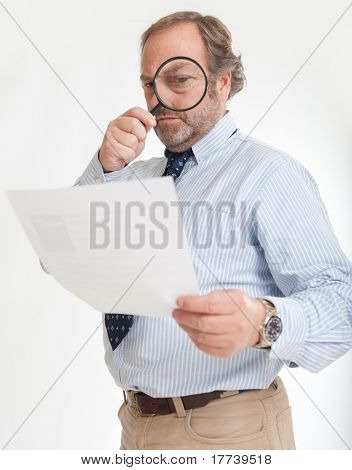 Man inspecting a document through a magnifying glass