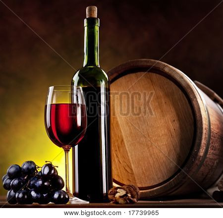 Still life with wine bottle, glass and oak barrels.