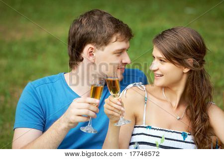Portrait of man and his girlfriend holding flutes with alcohol and looking at each other
