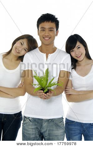 Young people on holding a small plant with two girl