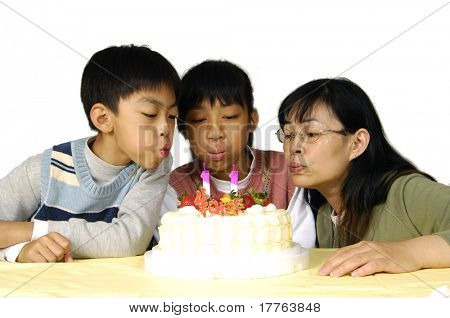 Family celebrating birthday- blowing out candles