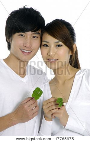 young attractive happy couple hand holding a green leaf