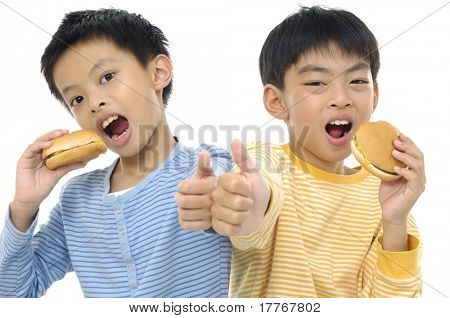 Smile two asian little boy eating a hamburger