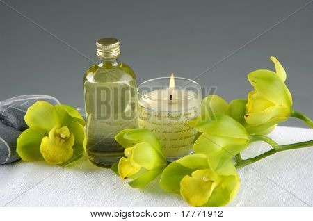 beauty and wellness concept-green orchid and candle and bottles with essential oil