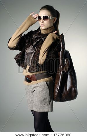 Beautiful fashion model with a bag posing on light background