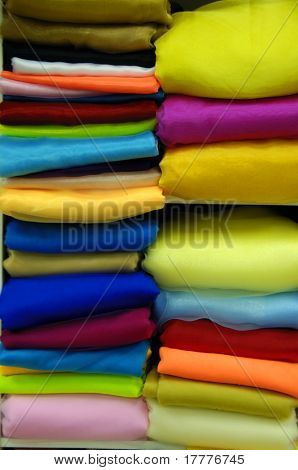 Stacks of colorful  sweaters isolated on white