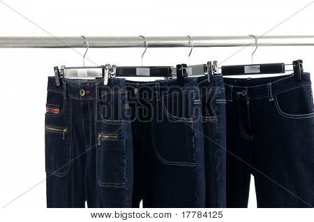 Blue jeans and trousers hanging