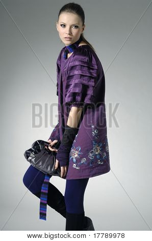 fashion model holding little purse in light background