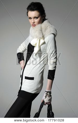 fashion model in autumn/winter clothes holding handbag posing in the studio