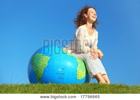 young curl woman in white clothes sitting on big inflatable globe on green lawn and smiling, blue sky
